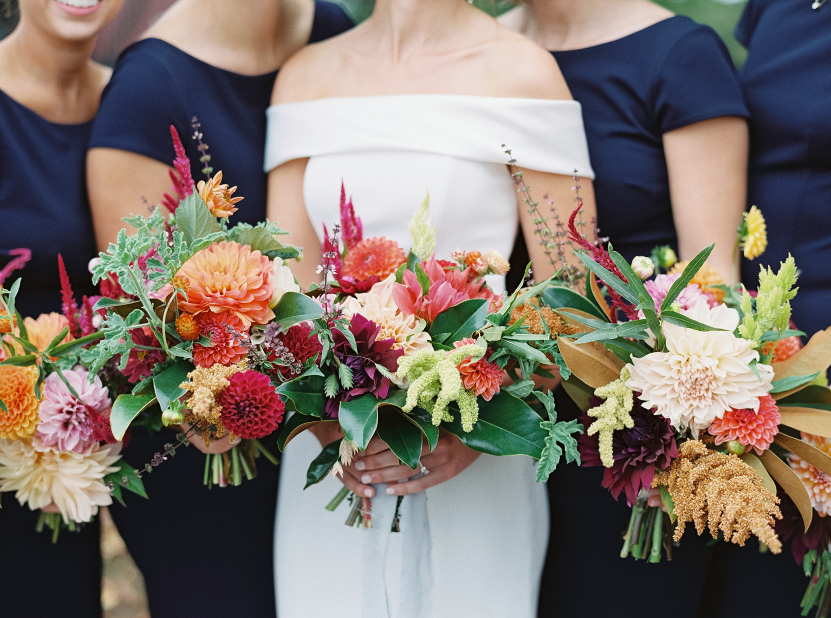bridal party holding various bright colored floral wedding bouquets