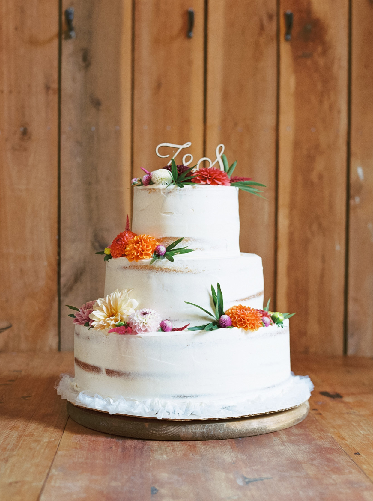 three tiered white frosted wedding cake with colorful floral accents