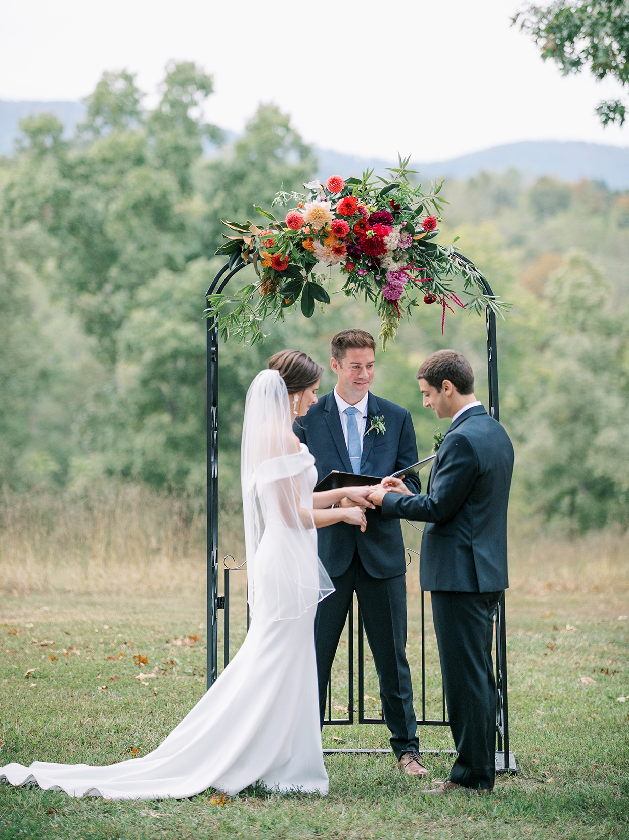 bride and groom stand outside next to metal wedding arch