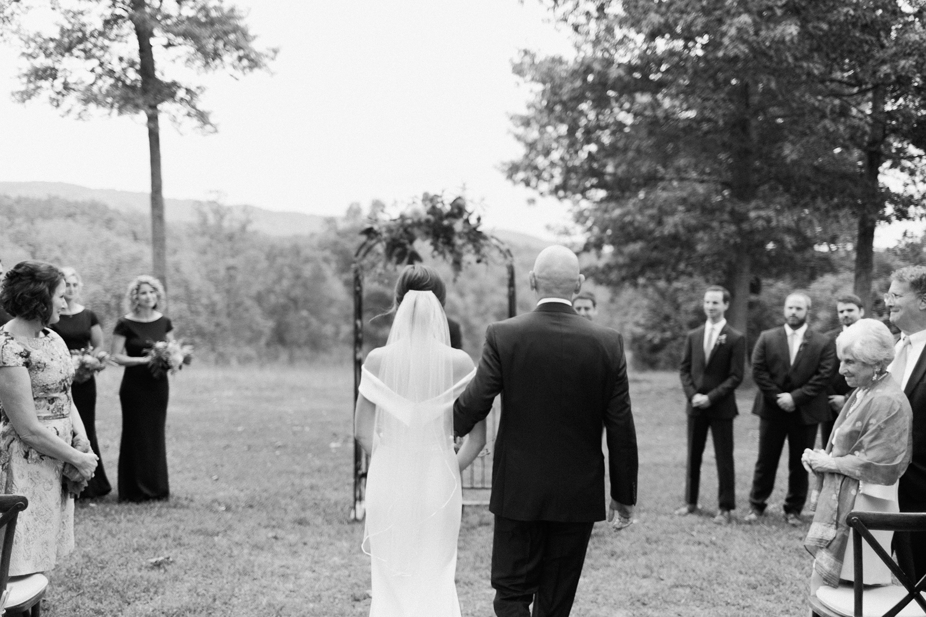 bride walks with father down processional aisle outside