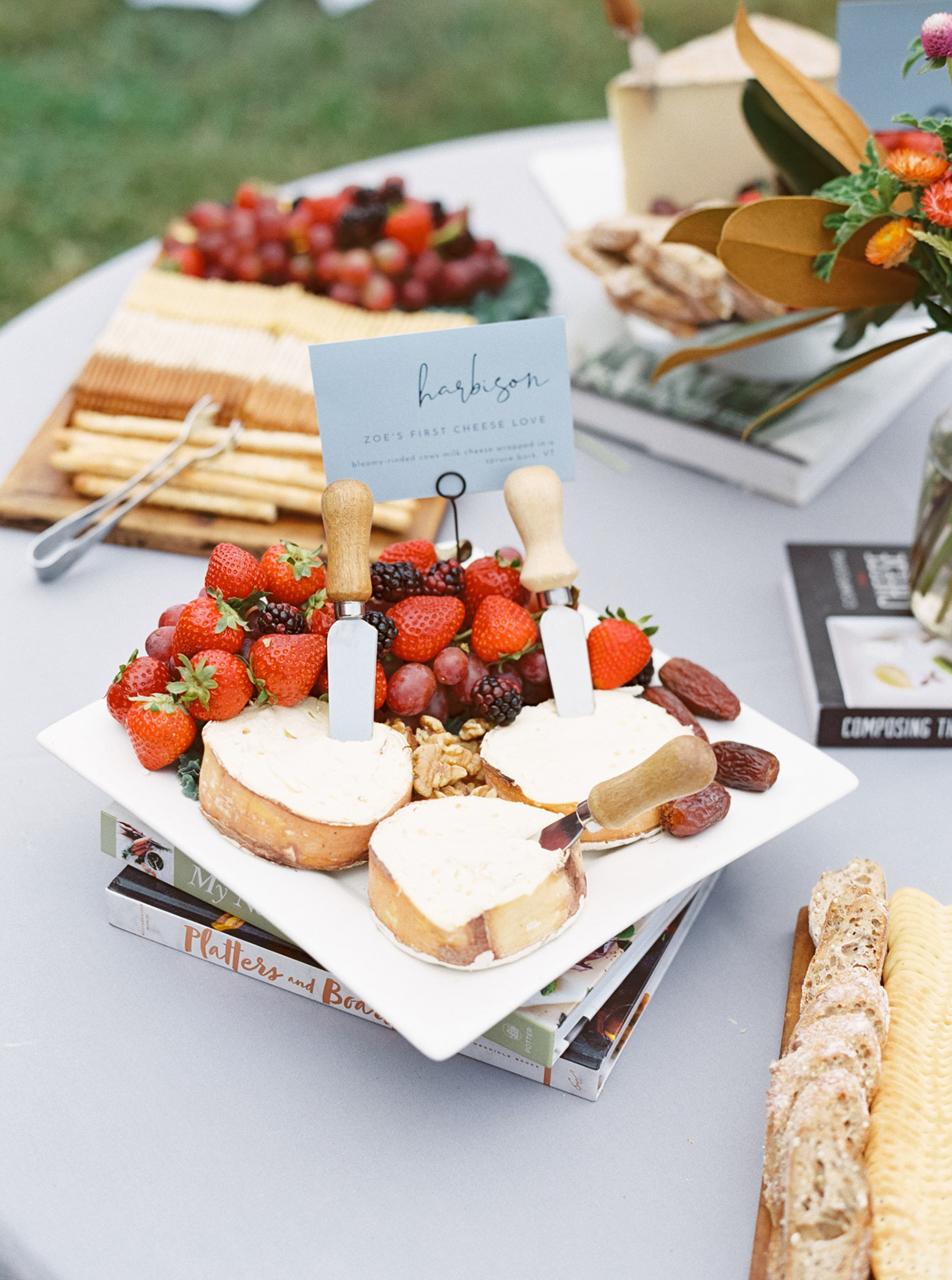 cheese and fruit wedding tray on top of book stack