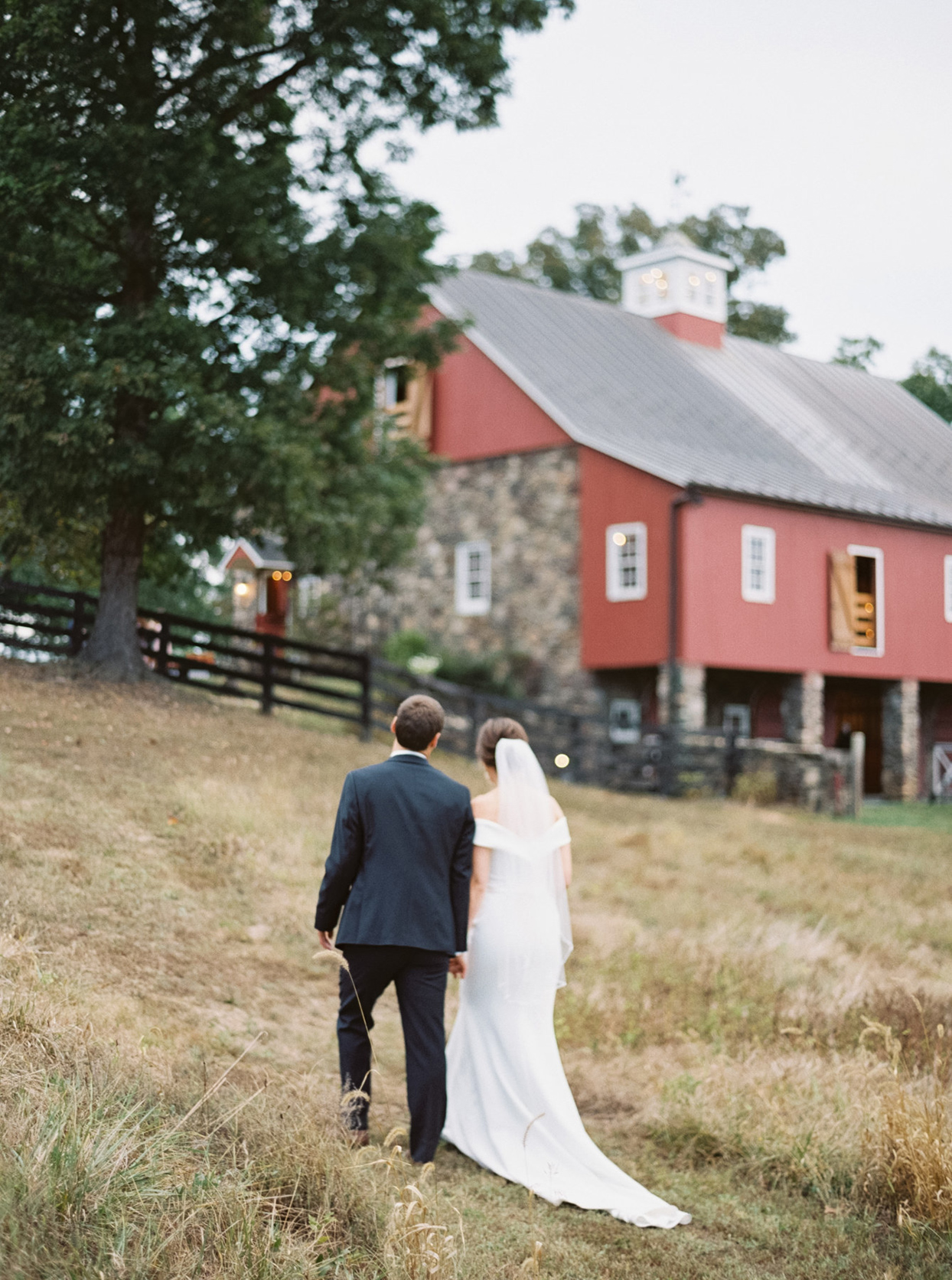 bride and groom walking up hill outside to wedding barn