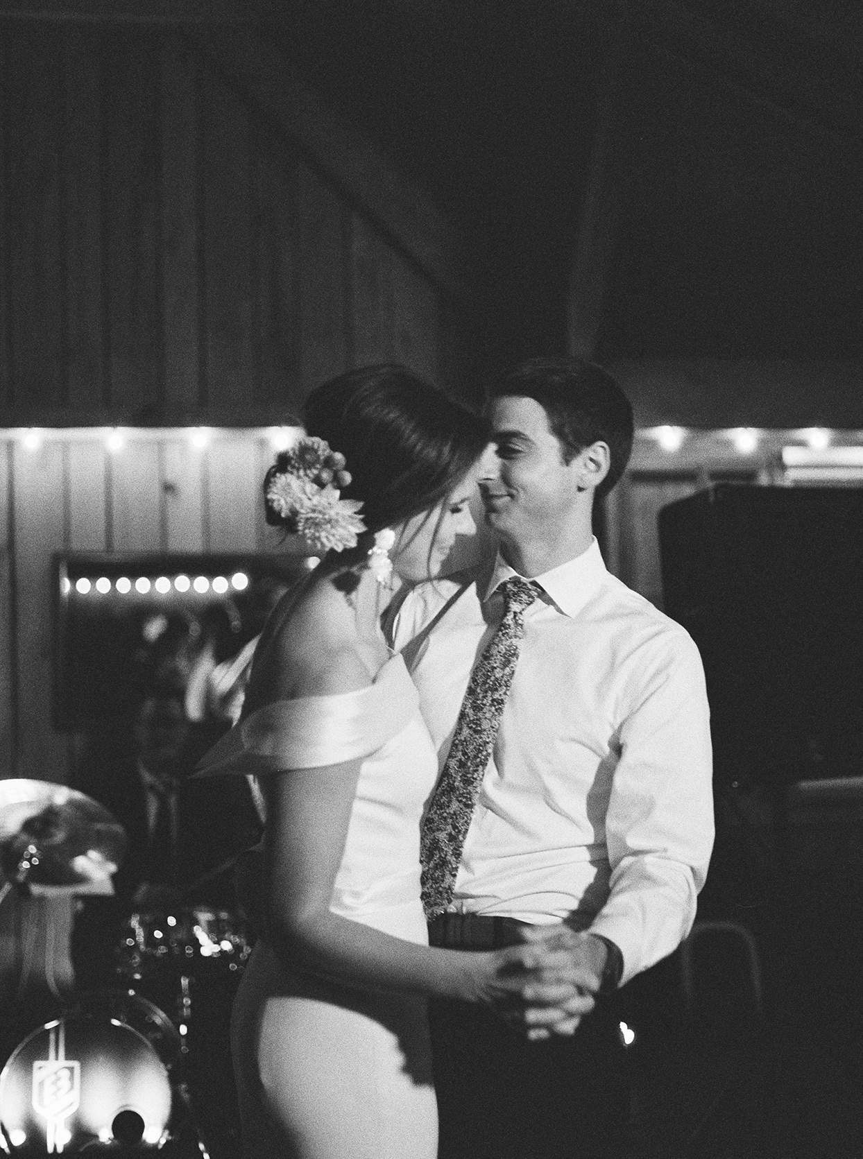 bride and groom smile during first dance inside barn area