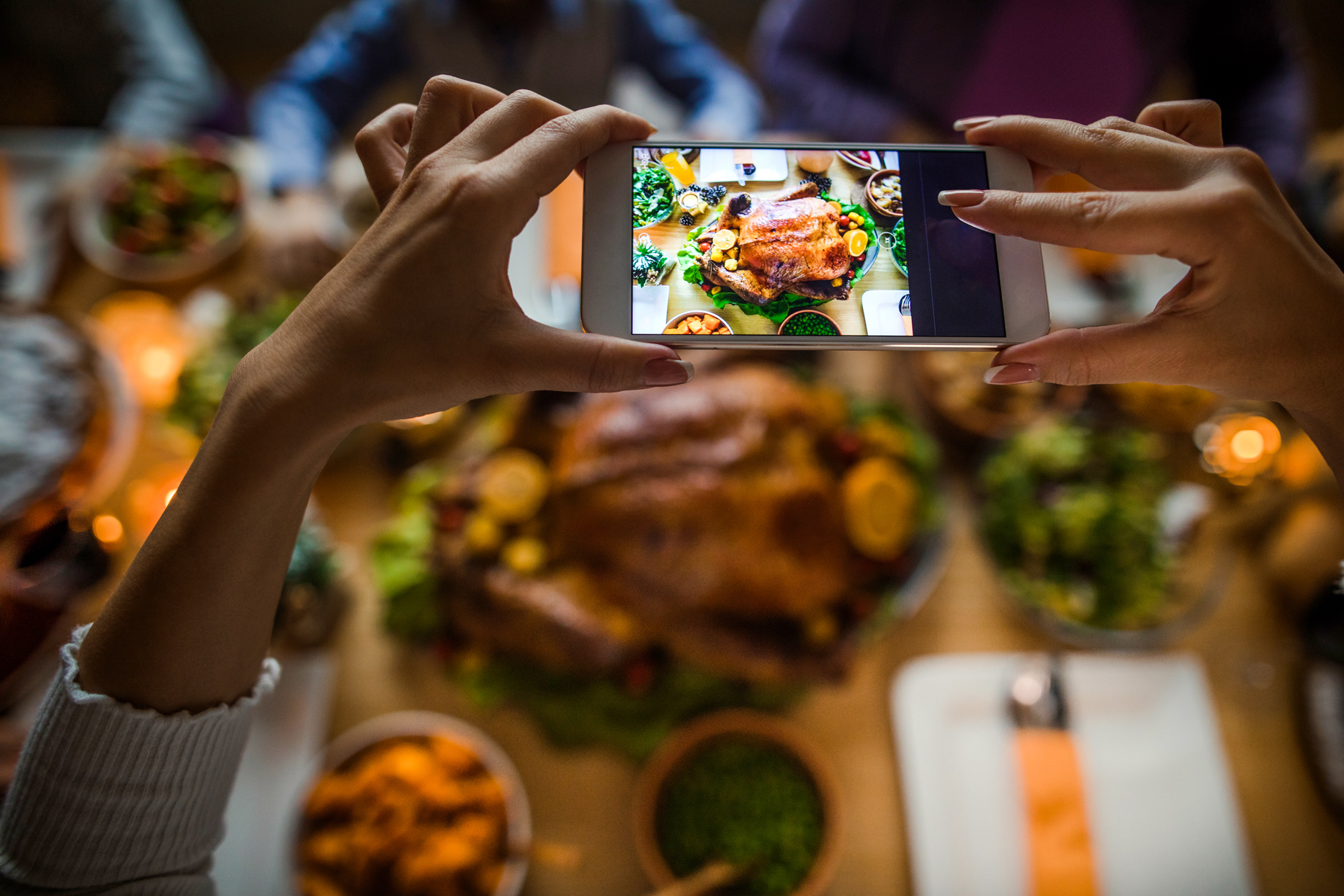 woman photographing thanksgiving meal with iphone
