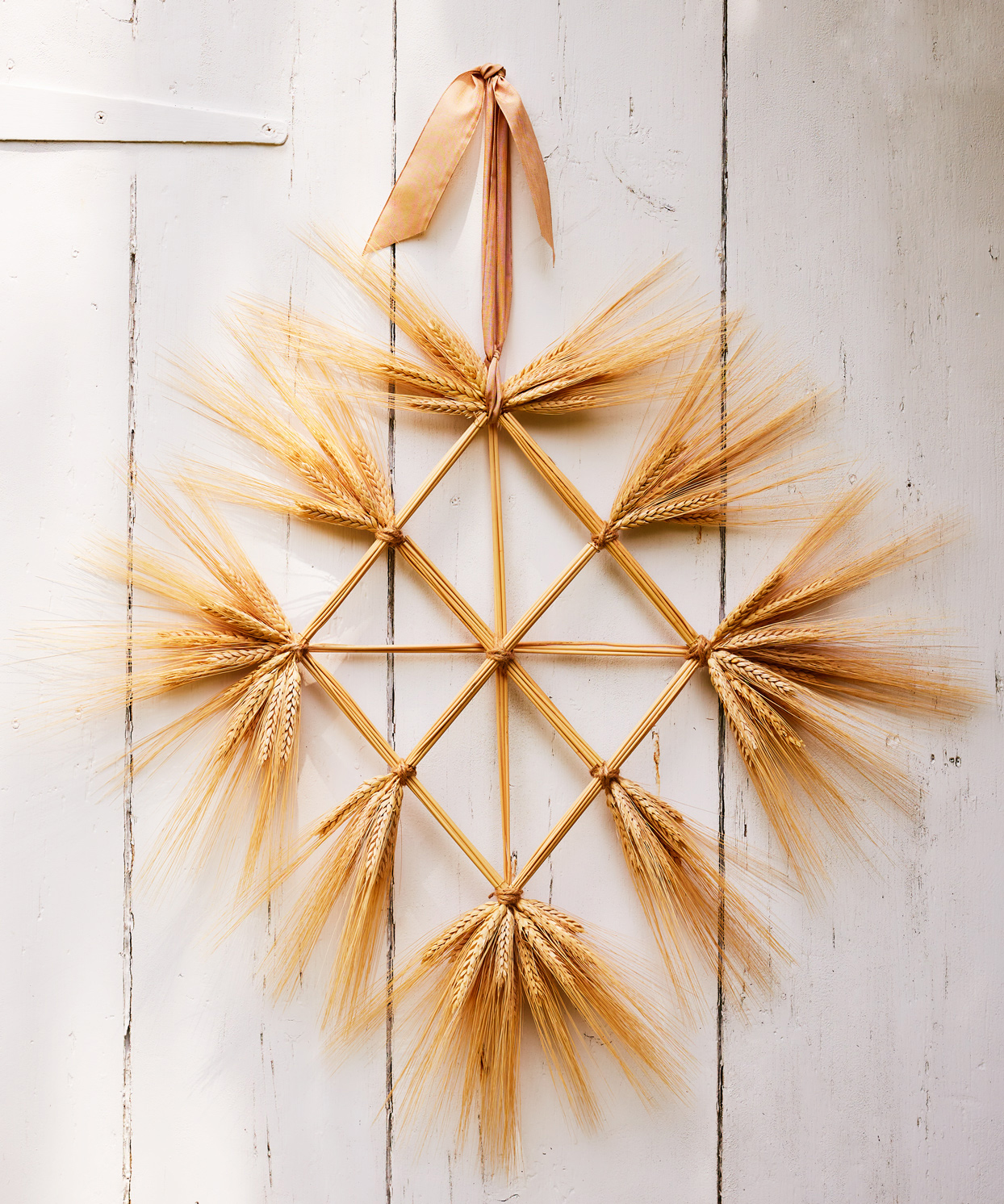 wheat grid wreath hanging from white barn door