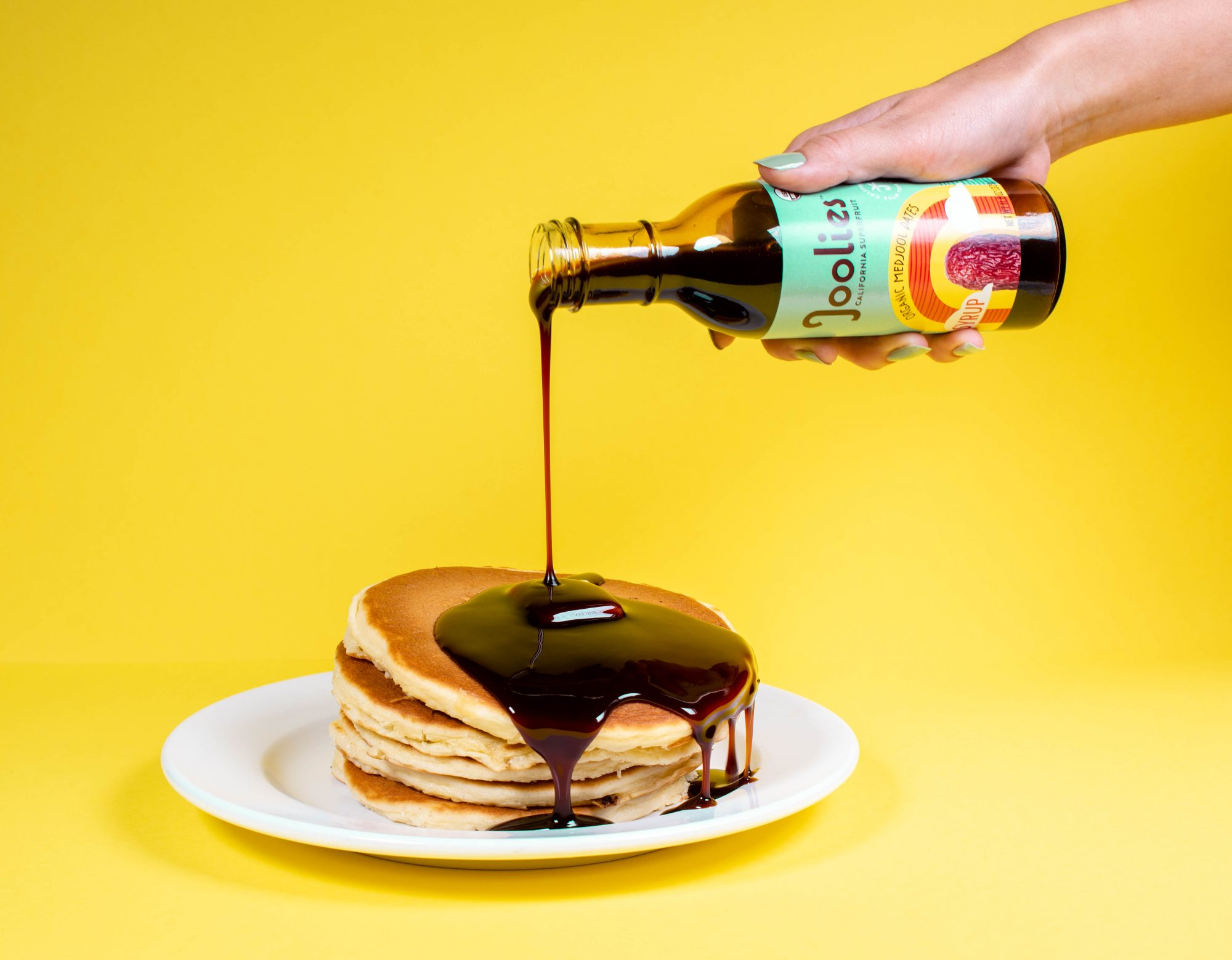 date syrup being poured onto pancakes