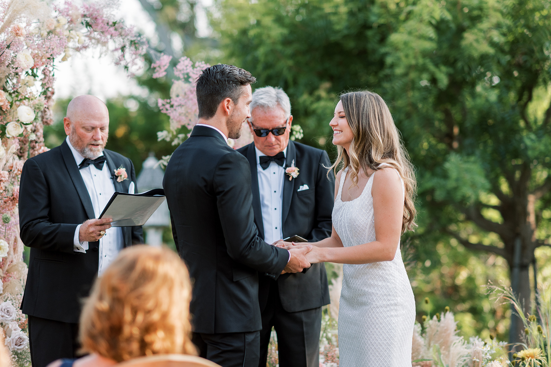 bride and groom exchanging vows during backyard wedding ceremony