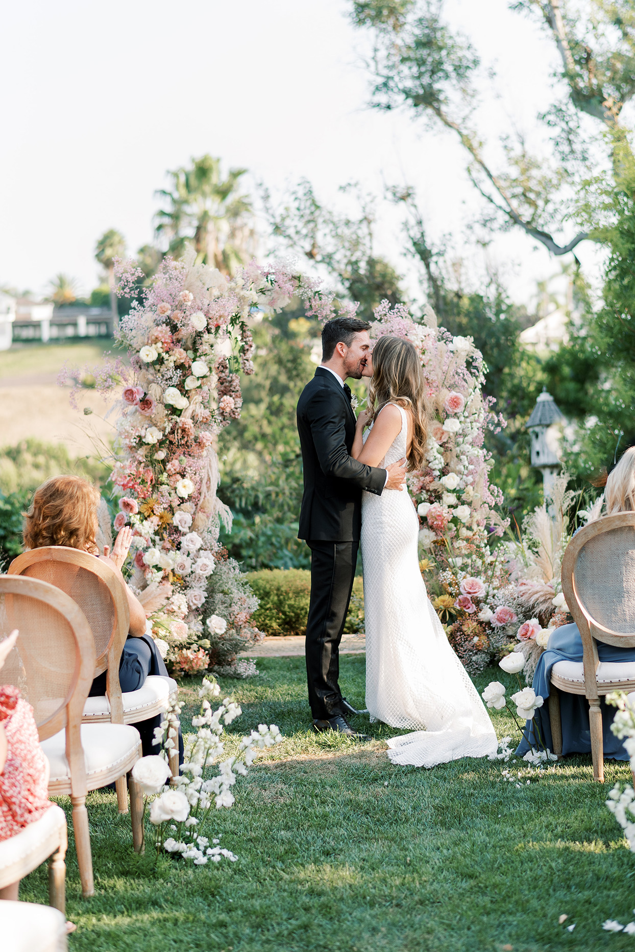 bride and groom share a kiss after backyard wedding ceremony