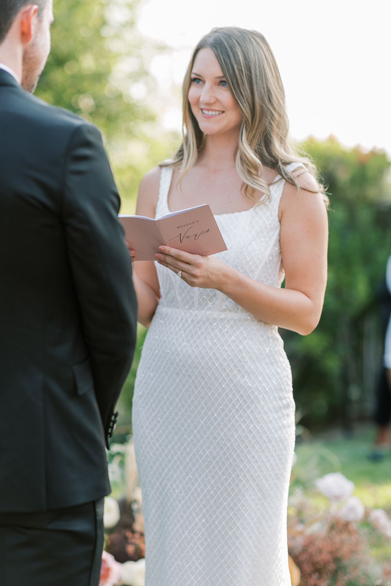 bride sharing vows with groom during backyard wedding ceremony