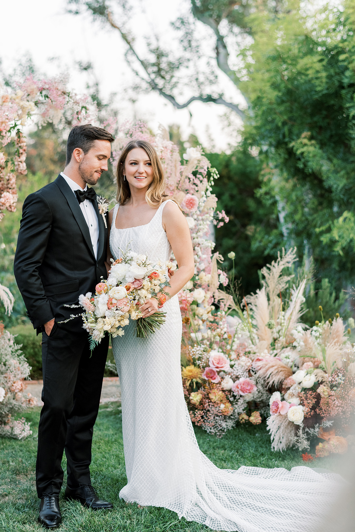bride and groom standing in backyard by floral arch