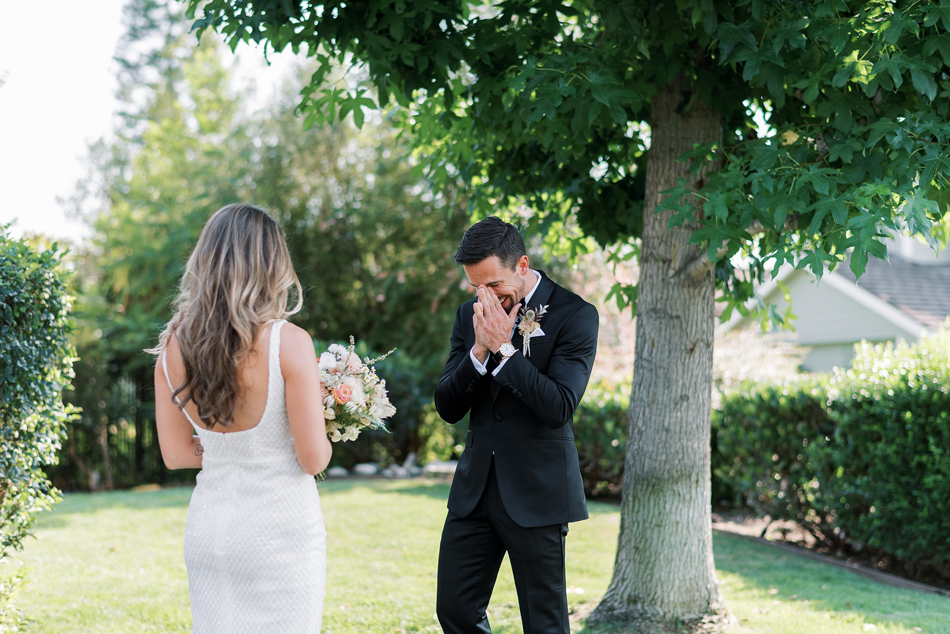 groom covering face with hands smiling after first look