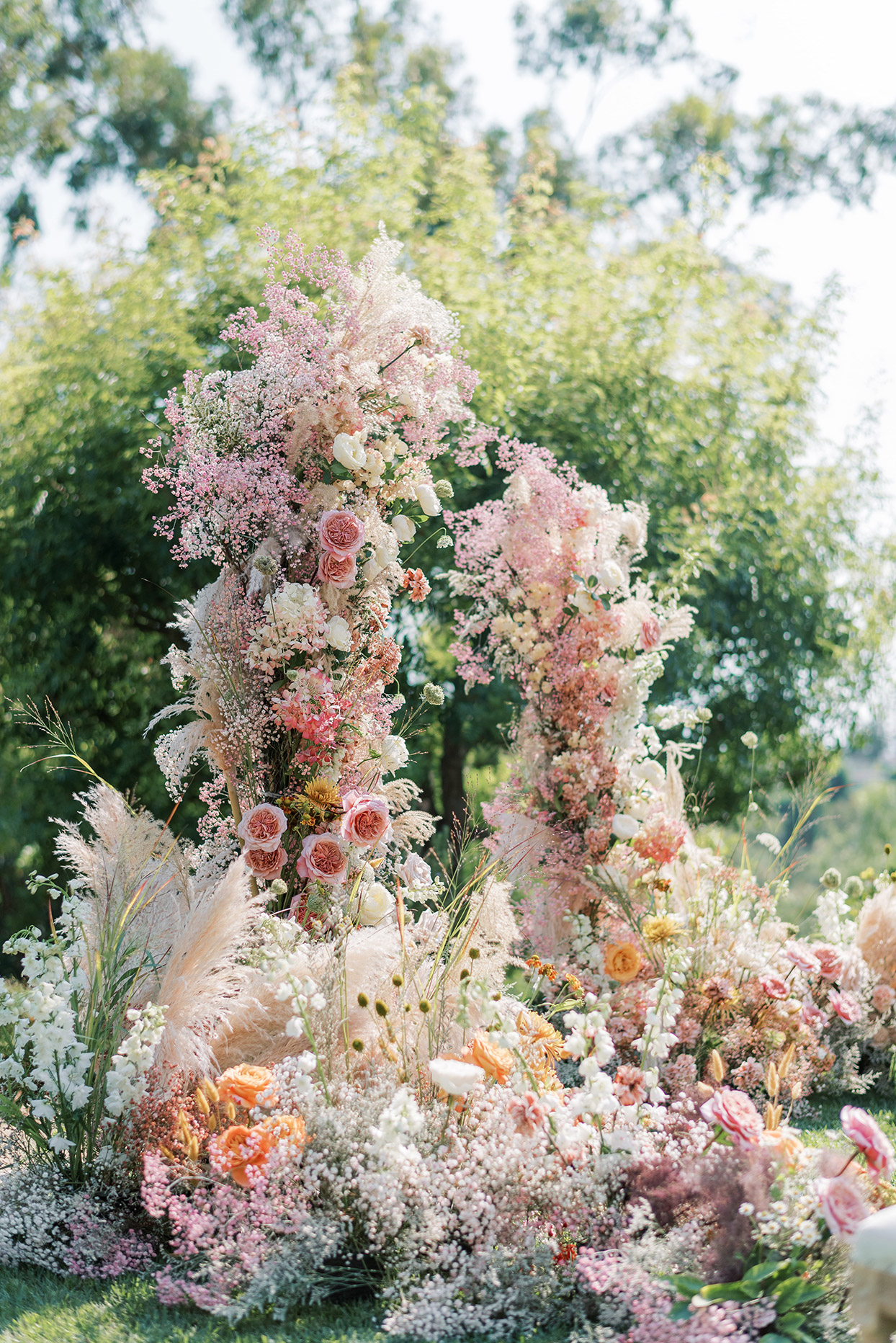 large pink floral wedding arch with various boho style foliage