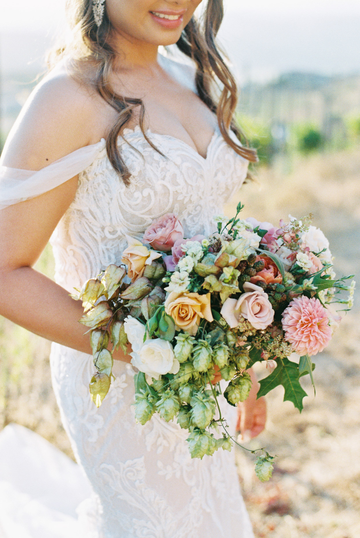 bride holding pink and orange themed wedding bouquet