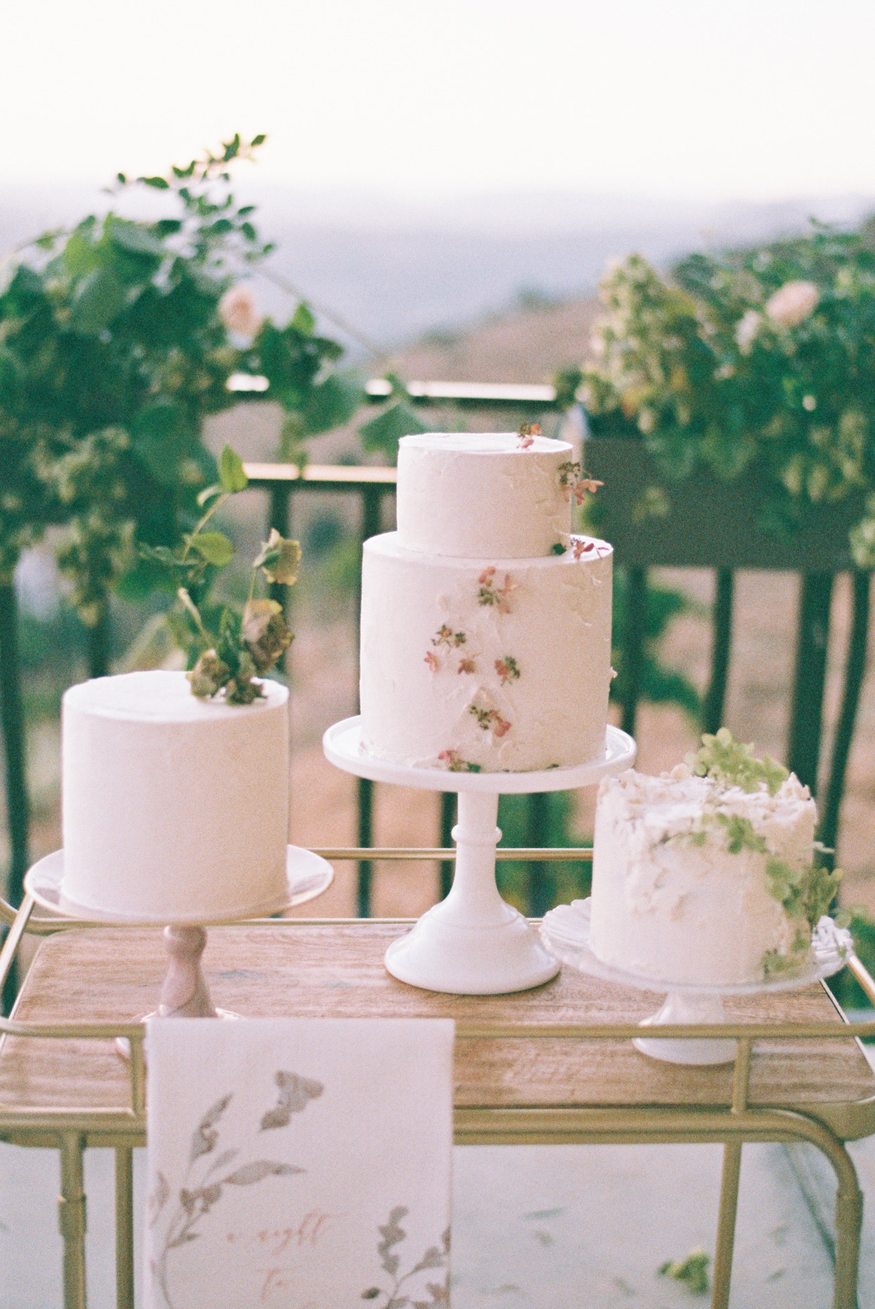 three simple wedding cakes on cart