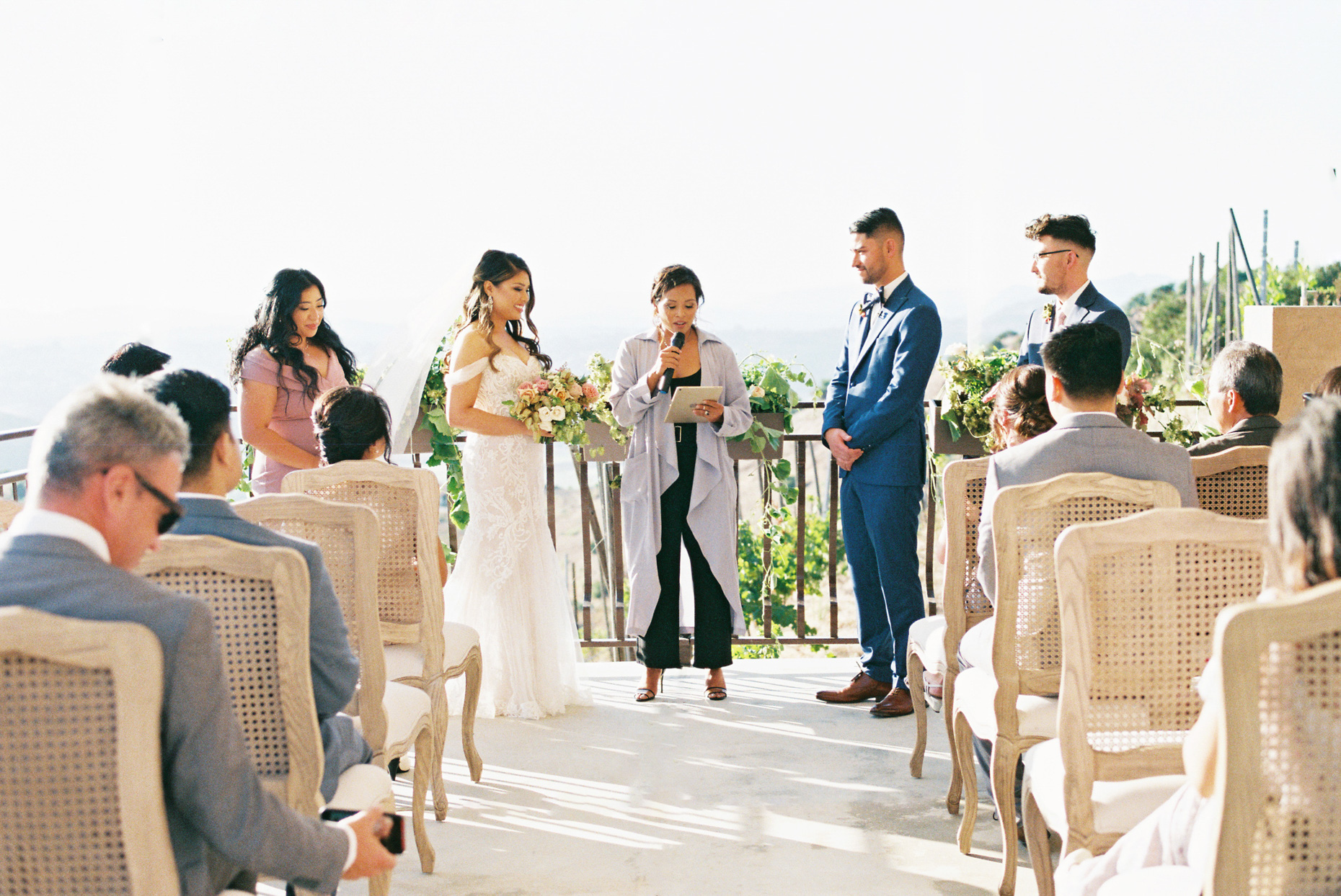 couple exchanging vows on deck overlooking vineyard