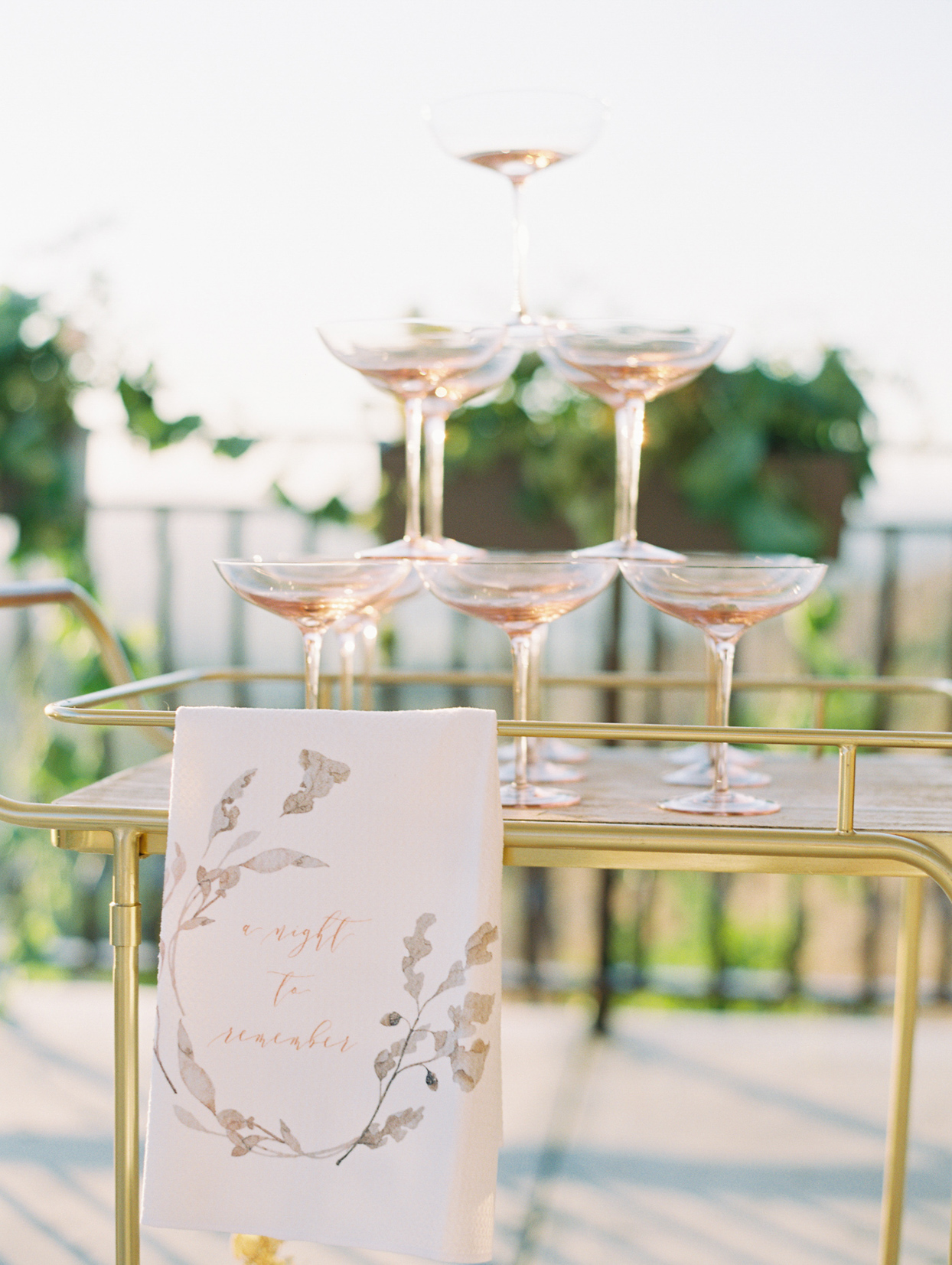 champagne tower on gold cart with calligraphy sign