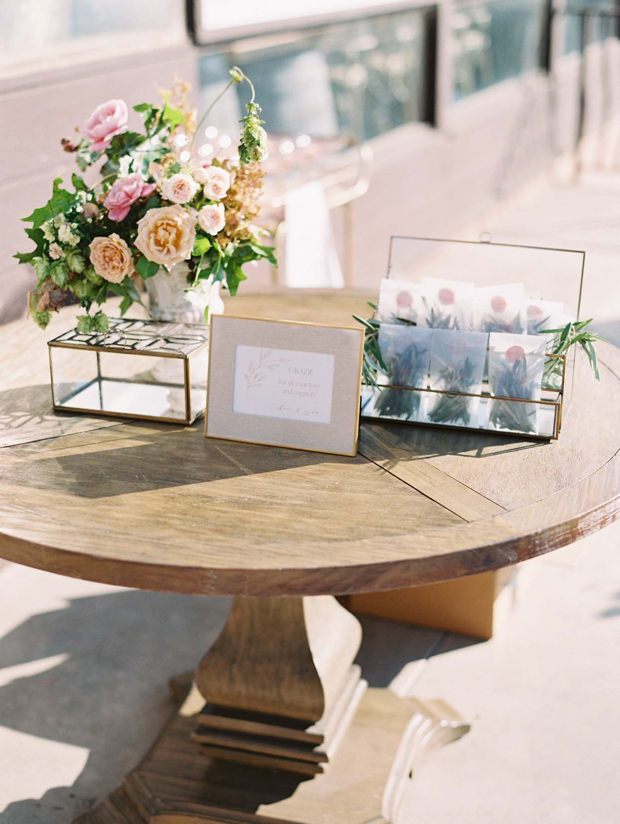 round wooden table with box of wedding favors