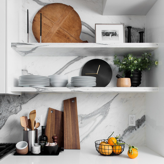 kitchen with marble backsplash and basket of oranges on countertop