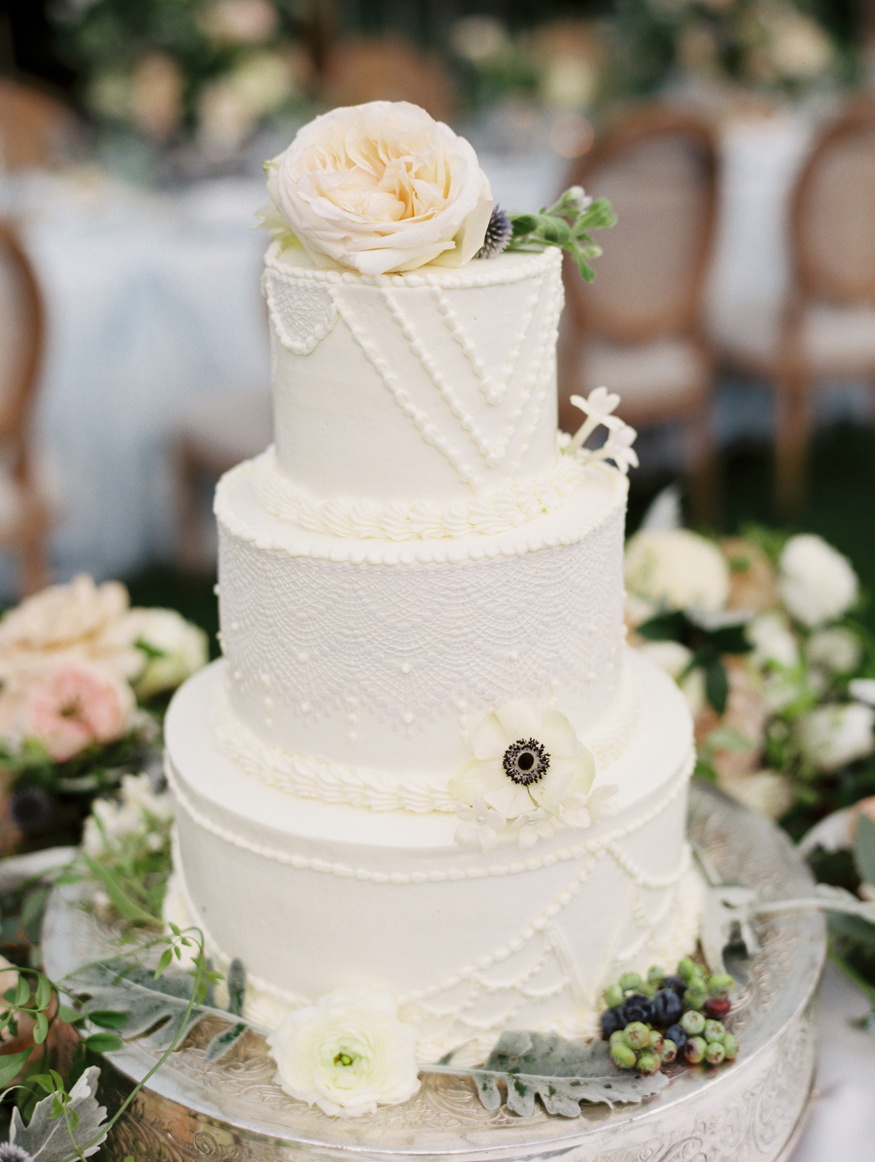 three tiered white frosted wedding cake with white floral and greenery accents