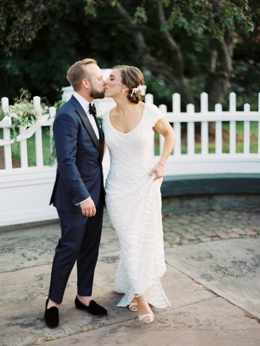 bride and groom share a kiss by white gate