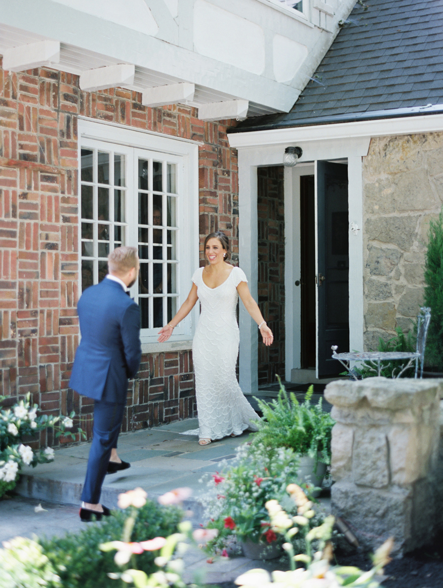 bride smiling showing groom first look outside