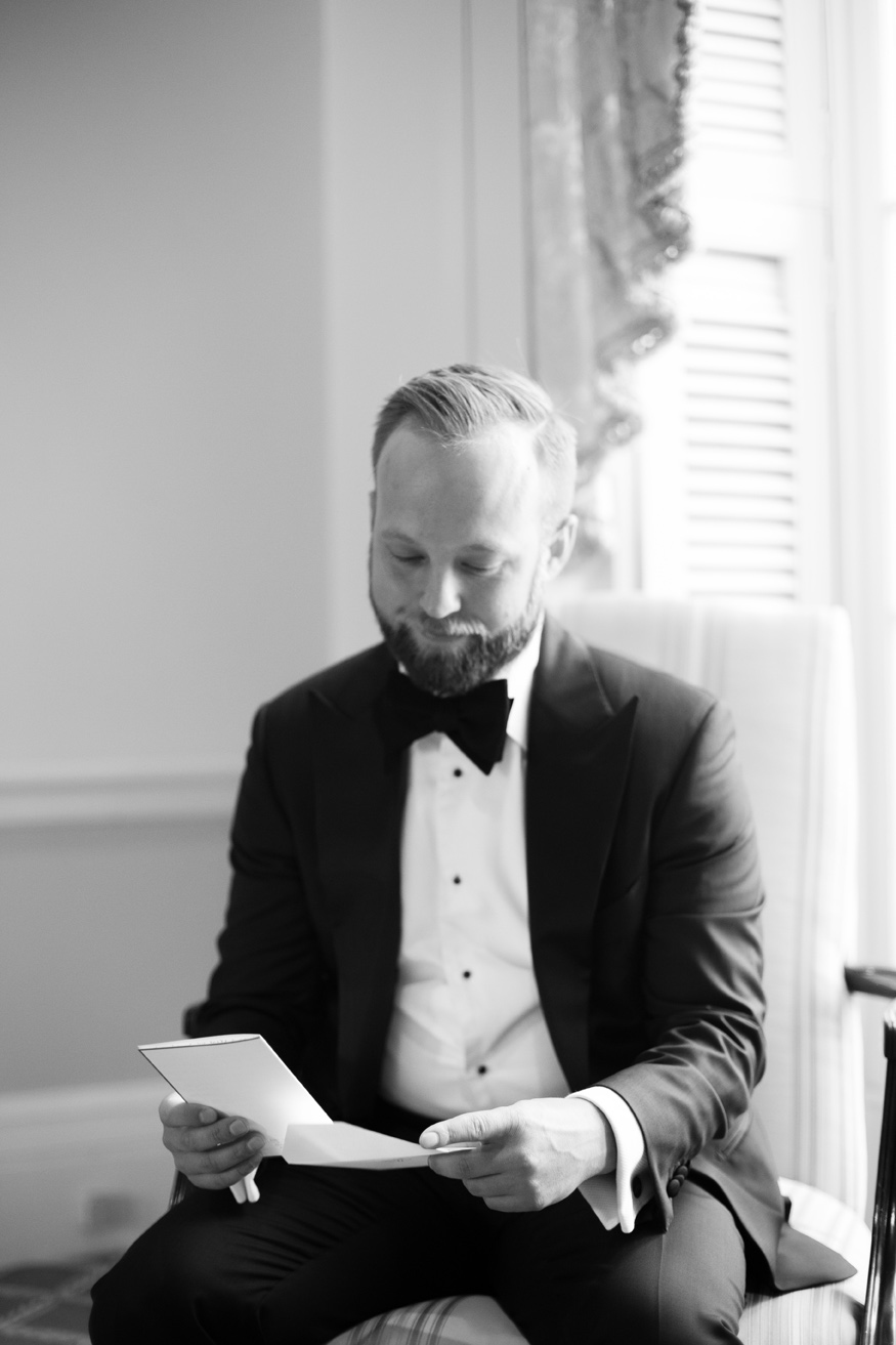 groom sitting reading card before ceremony
