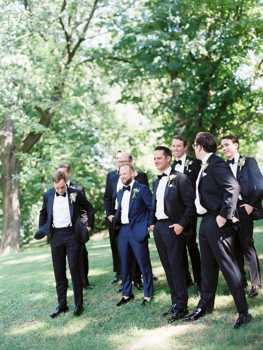 groom smiling on small hillside with groomsmen
