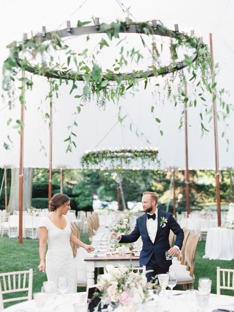 bride and groom under large white wedding reception tent