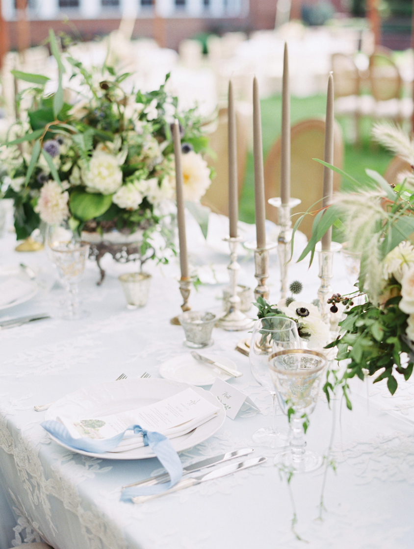 long white linen covered reception tables with tapper candles