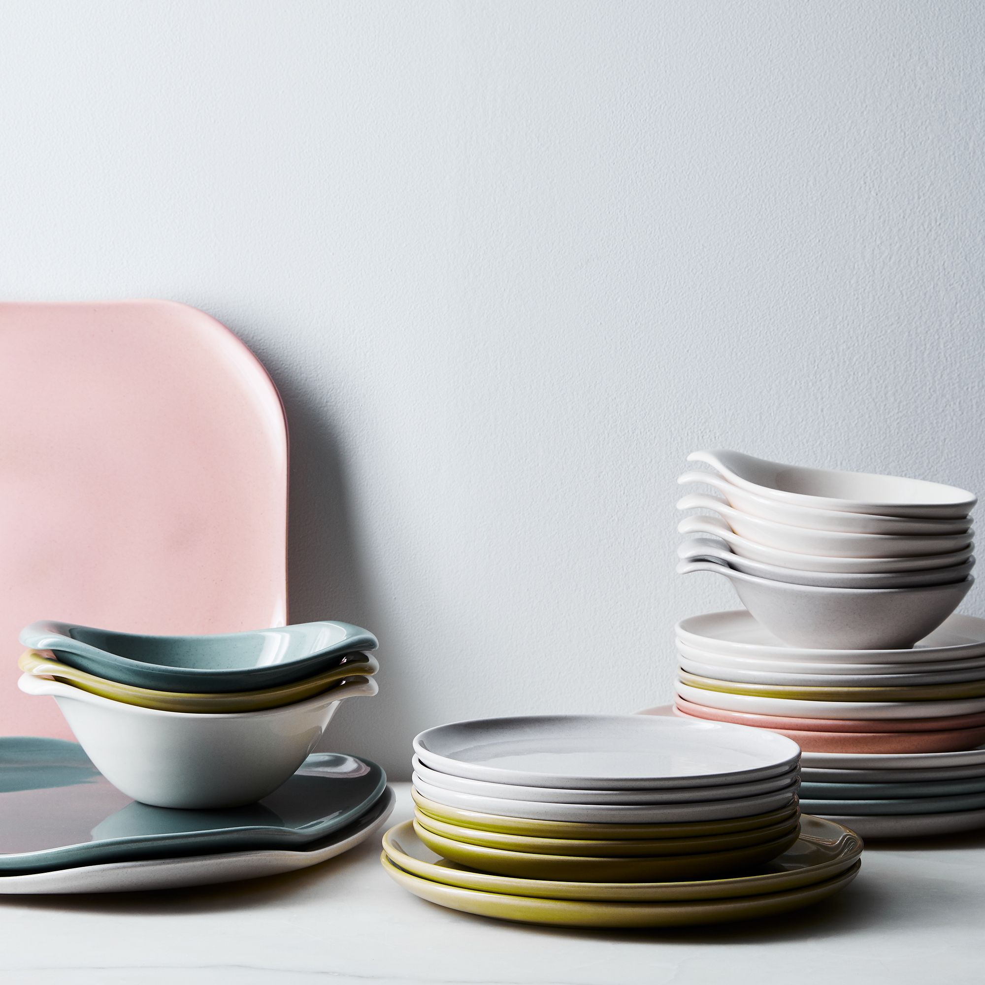 Stacks of Russel Wright dinnerware in a variety of colors