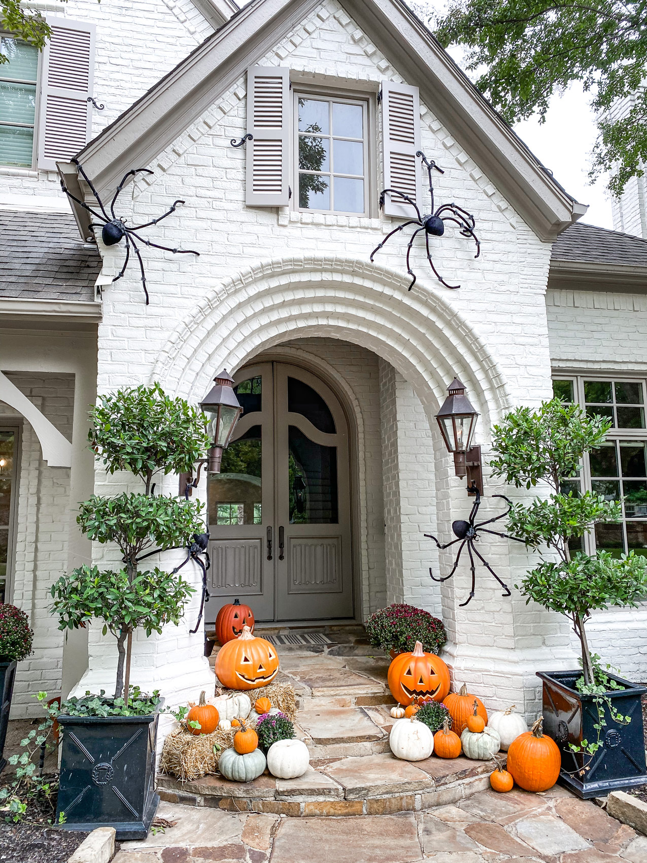 side view of fall porch with large spiders hay and pumpkins