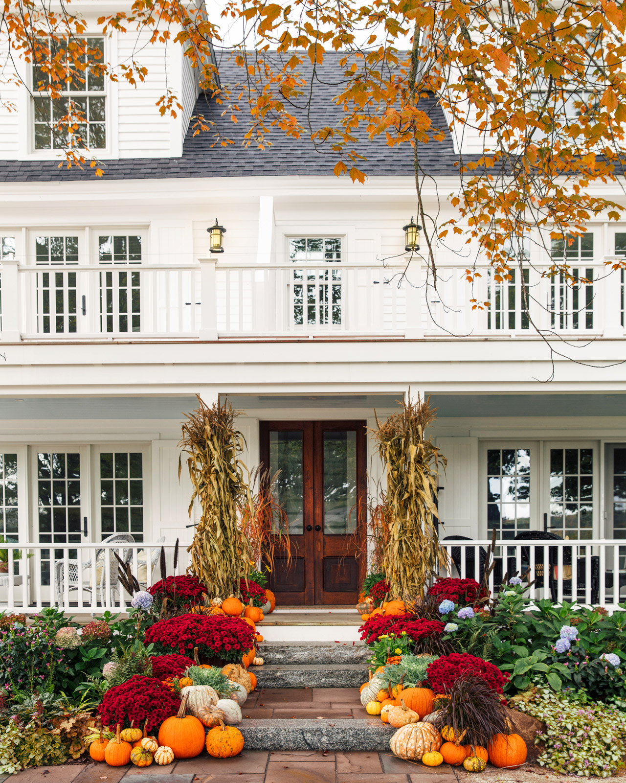 fall porch with colorful florals pumpkins and ghourds