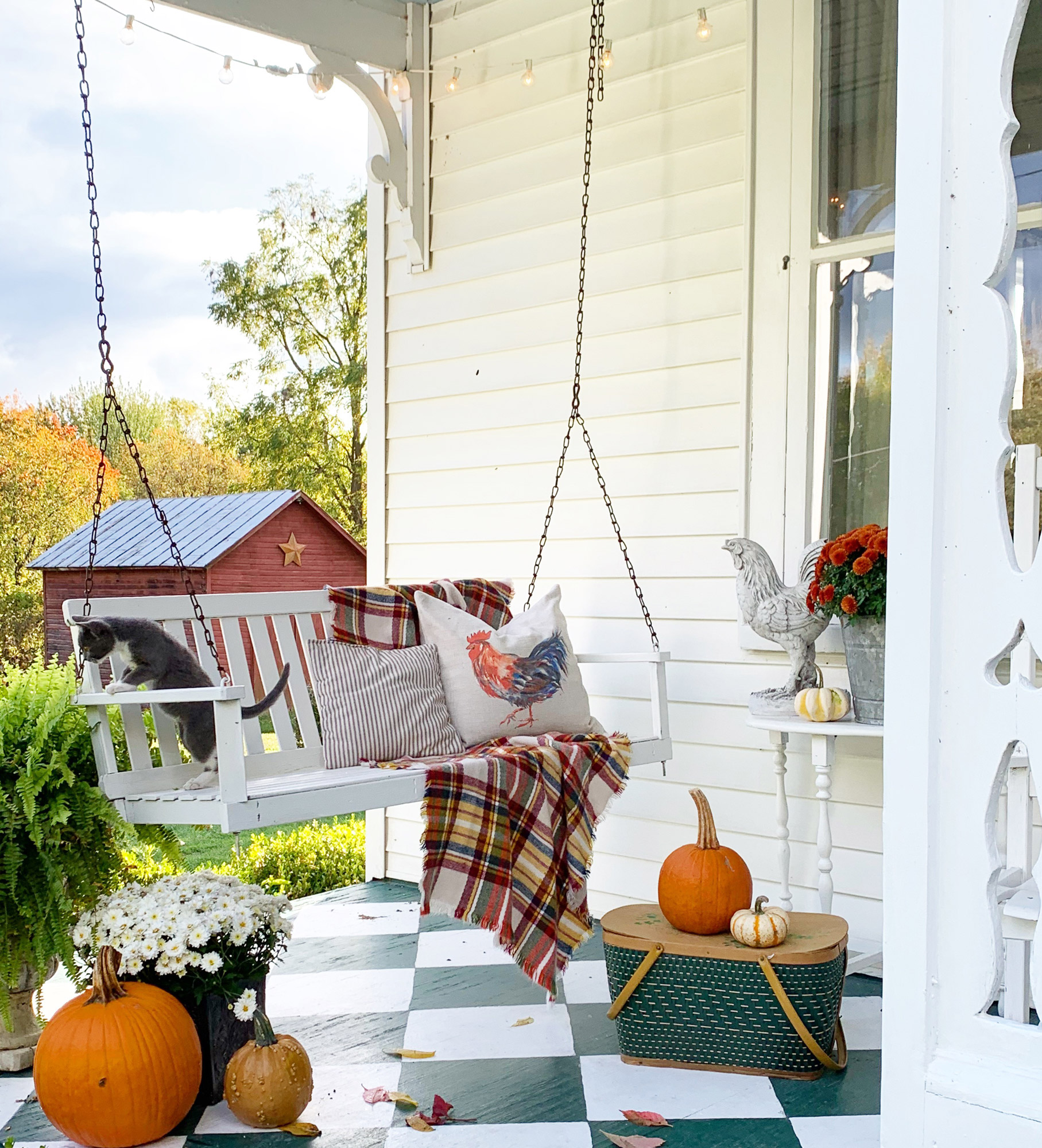 fall porch swing with plaid throw flowers and pumpkins