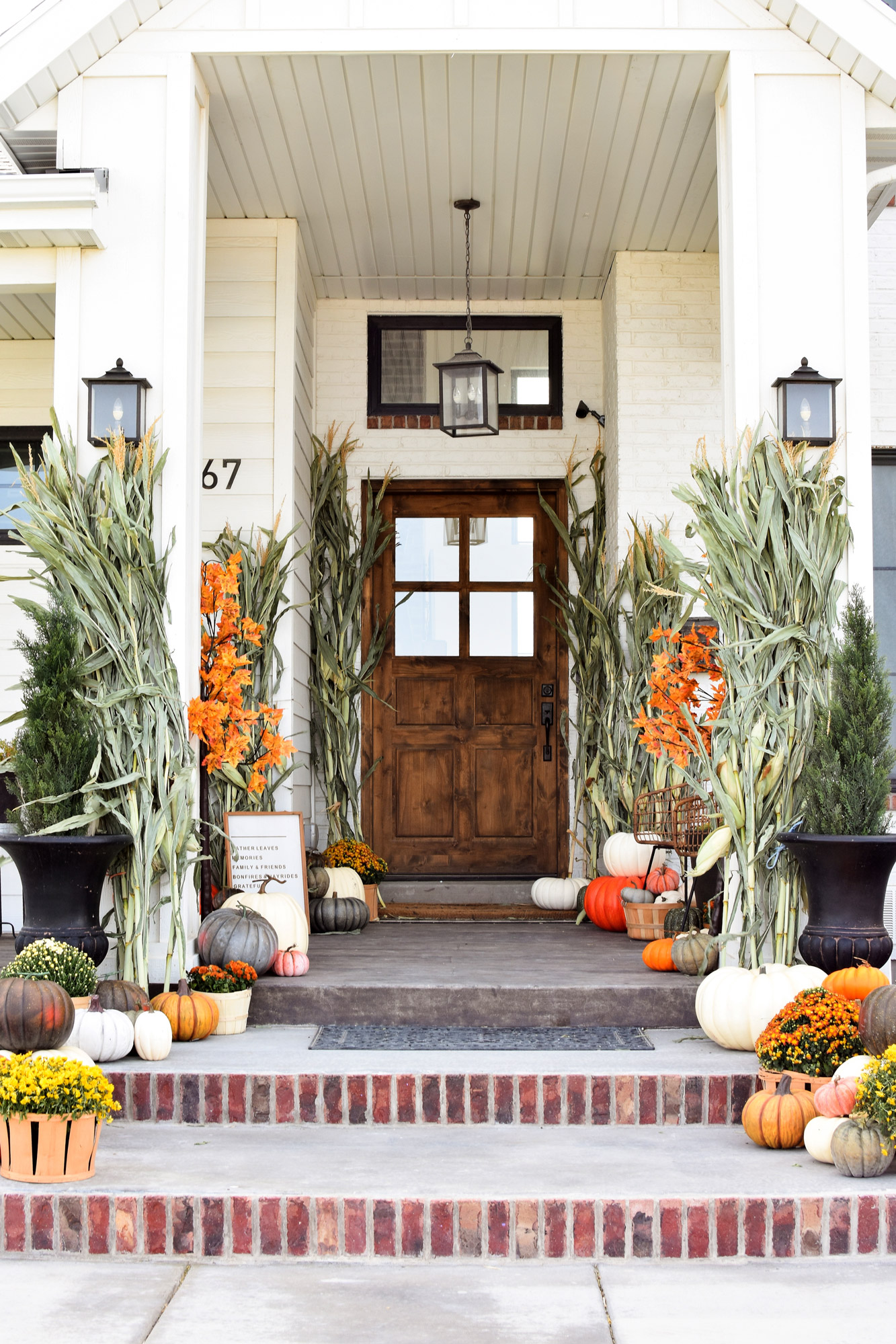 fall porch with dried corn husks and brightly florals pumpkins