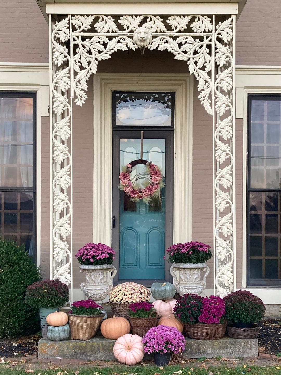 fall porch with purple mums and pumpkins