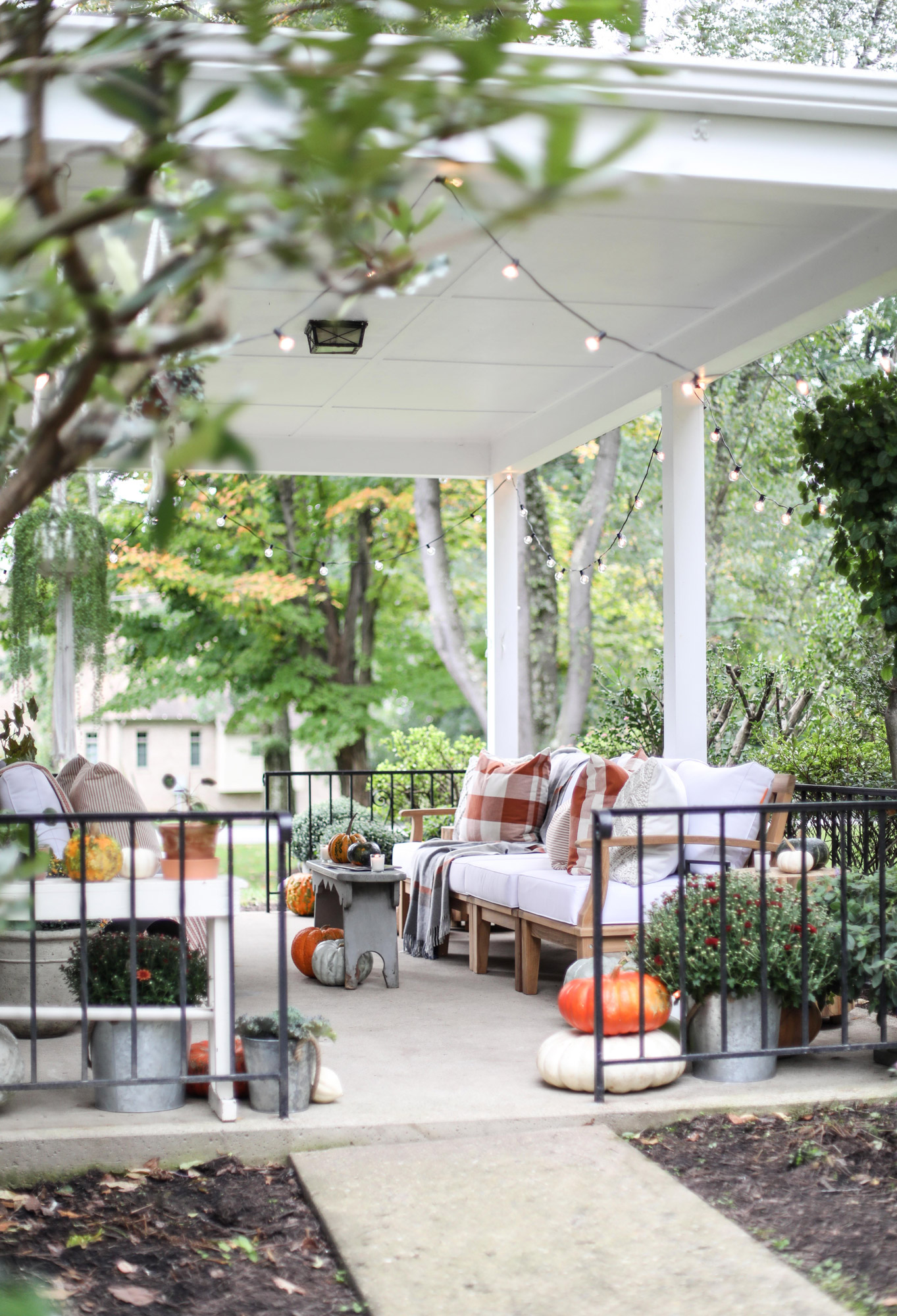 fall porch throw blankets twinkling lights pumpkins and mums