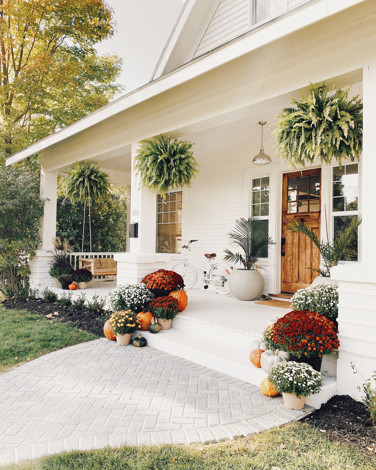 fall porch with colorful mums pumpkins gourds