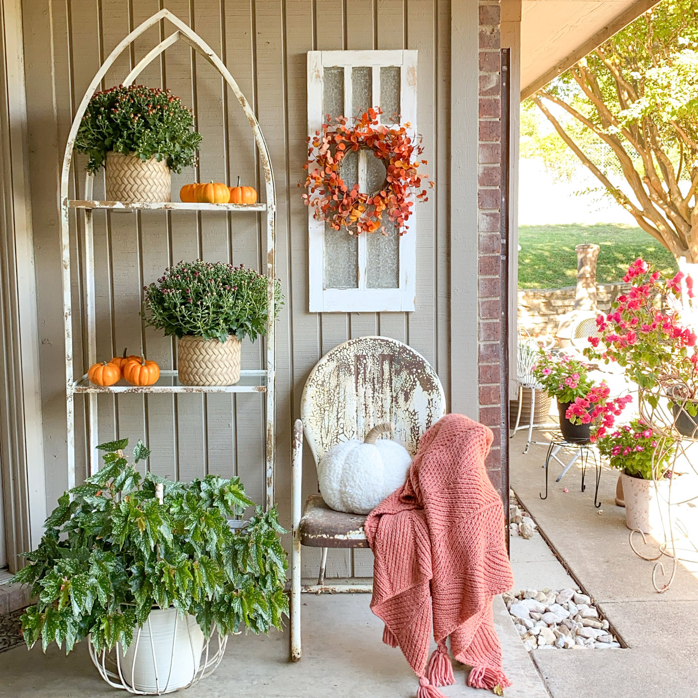fall porch weathered shelves and chair pumpkins and mums