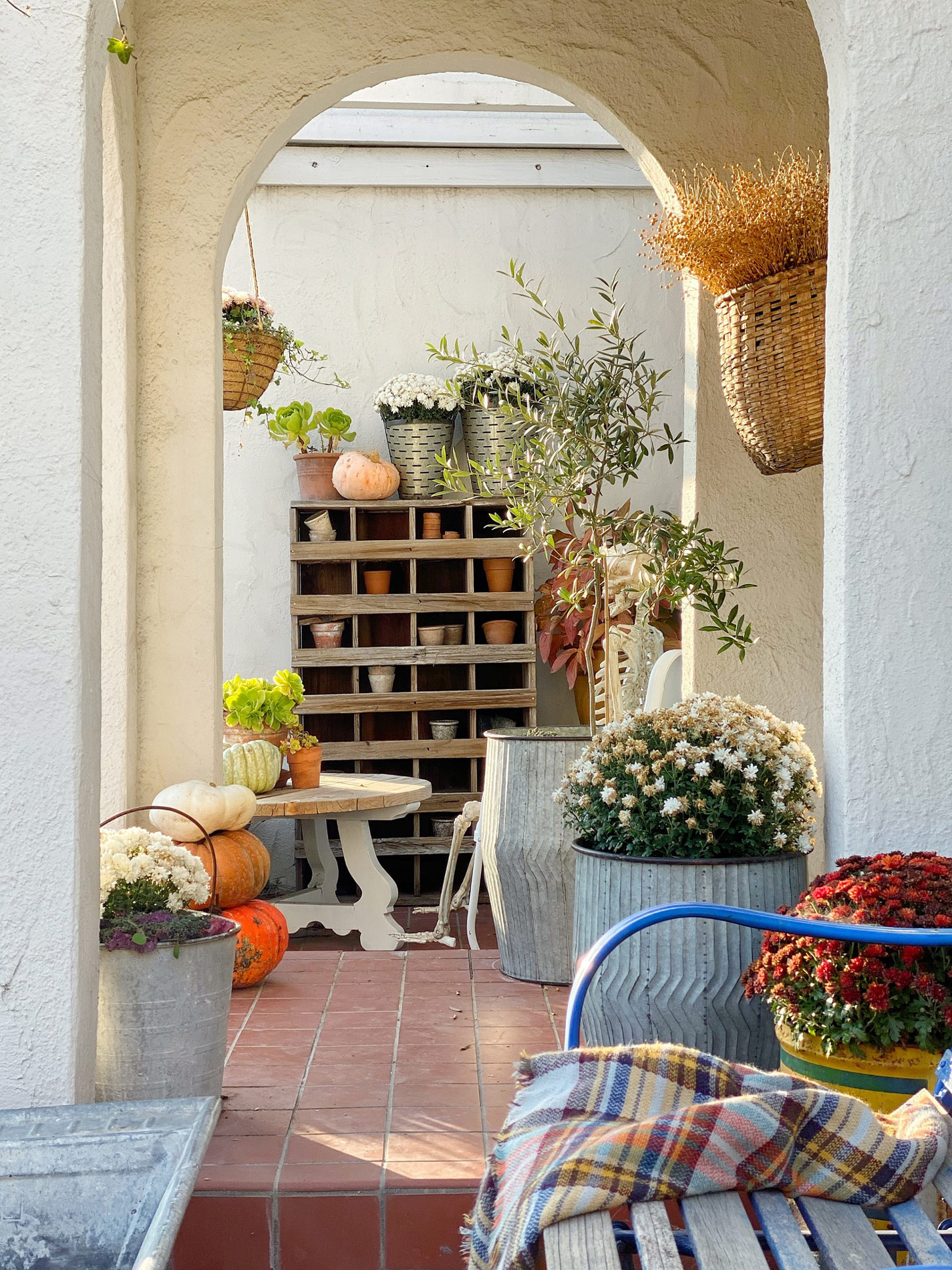 rustic fall porch with pumpkins and mums