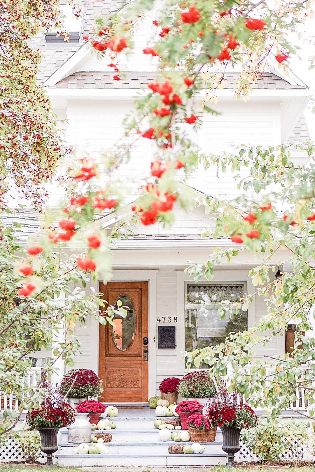 fall porch with green pumpkins and burgundy mums