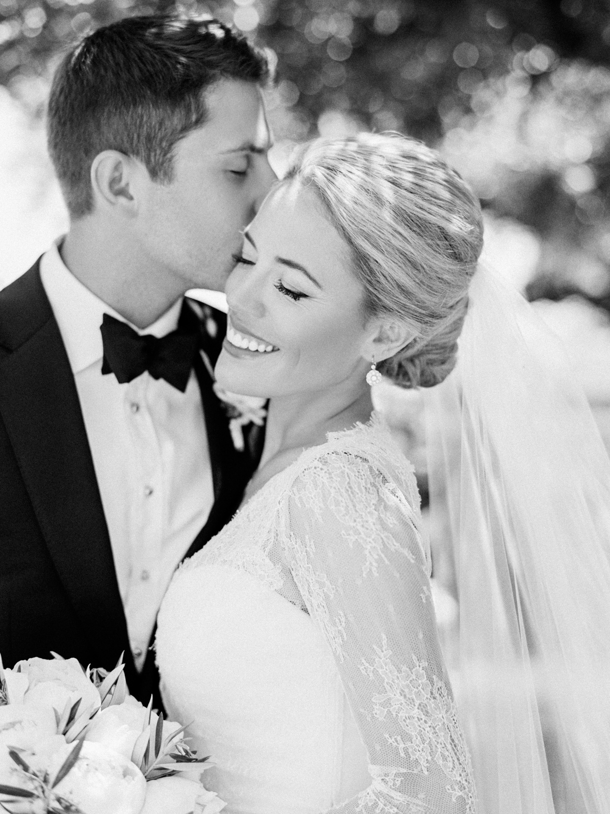 groom kissing bride during first look