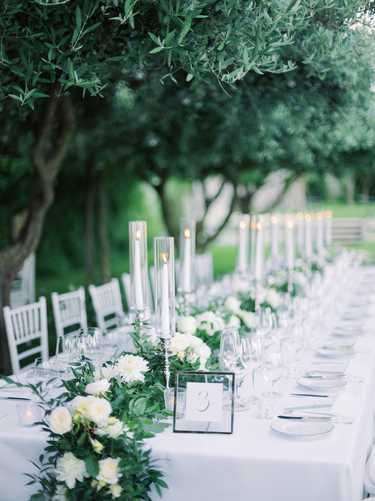 long white elegant wedding table with floral garland and candles