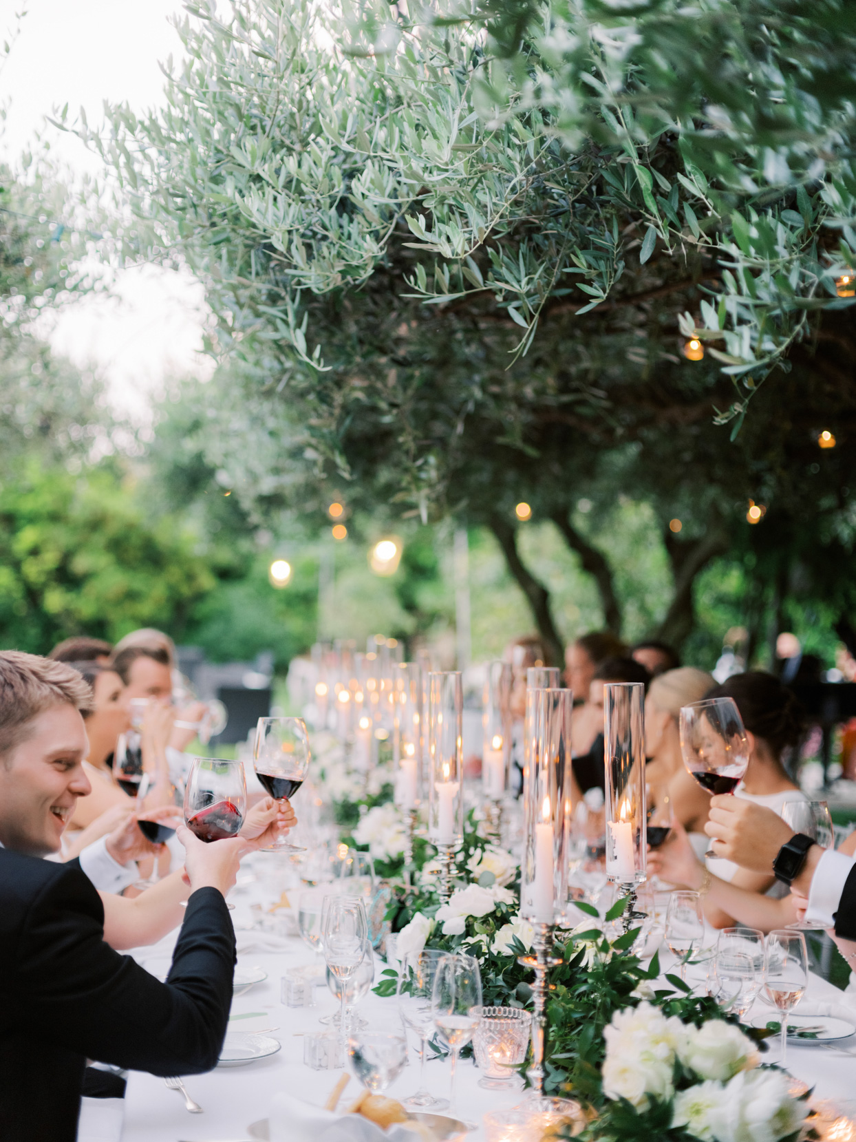 guests toasting at long white wedding table