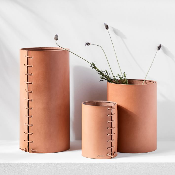 three leather-wrapped vases