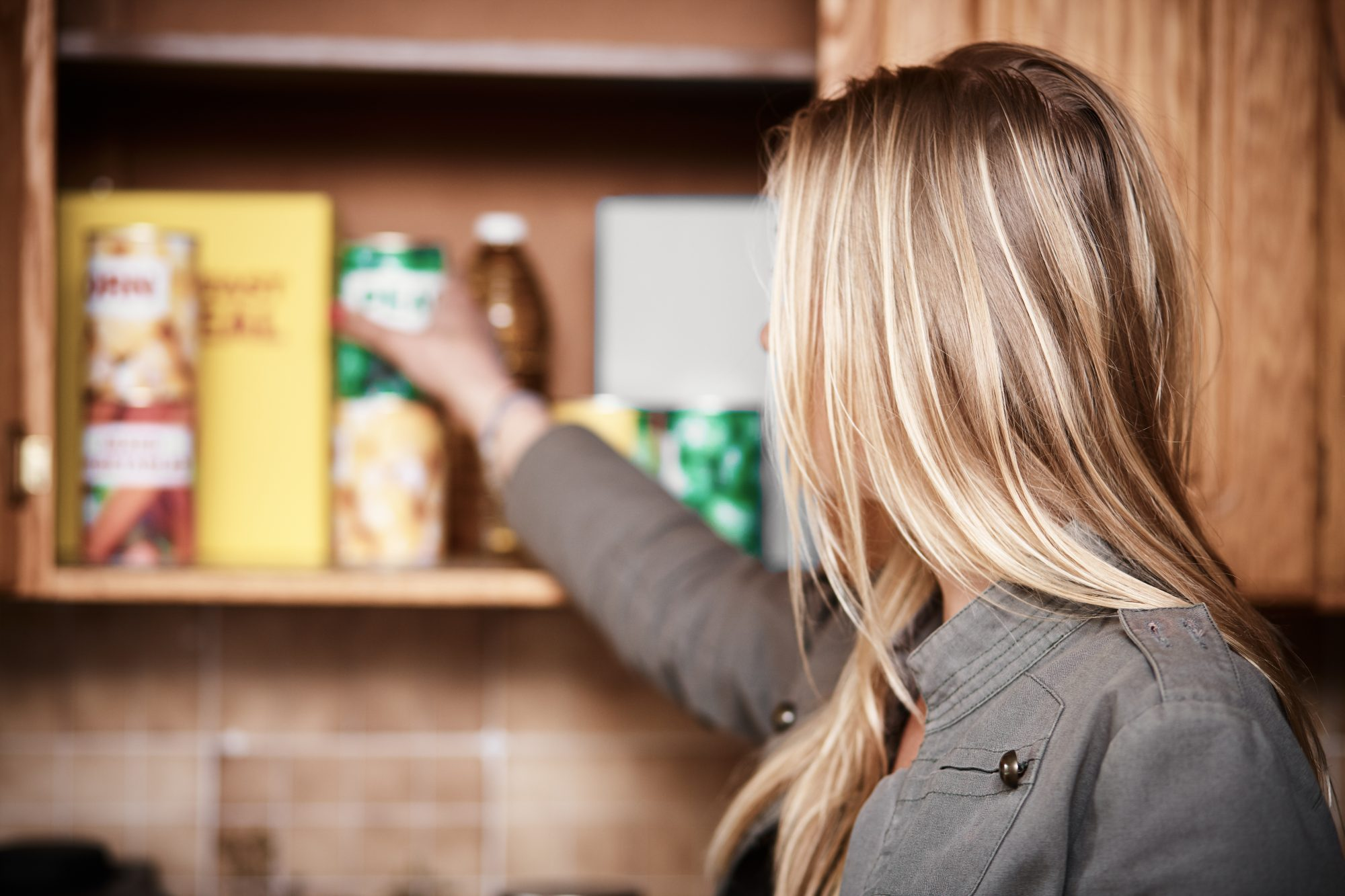woman reaching into kitchen cupboard for canned food