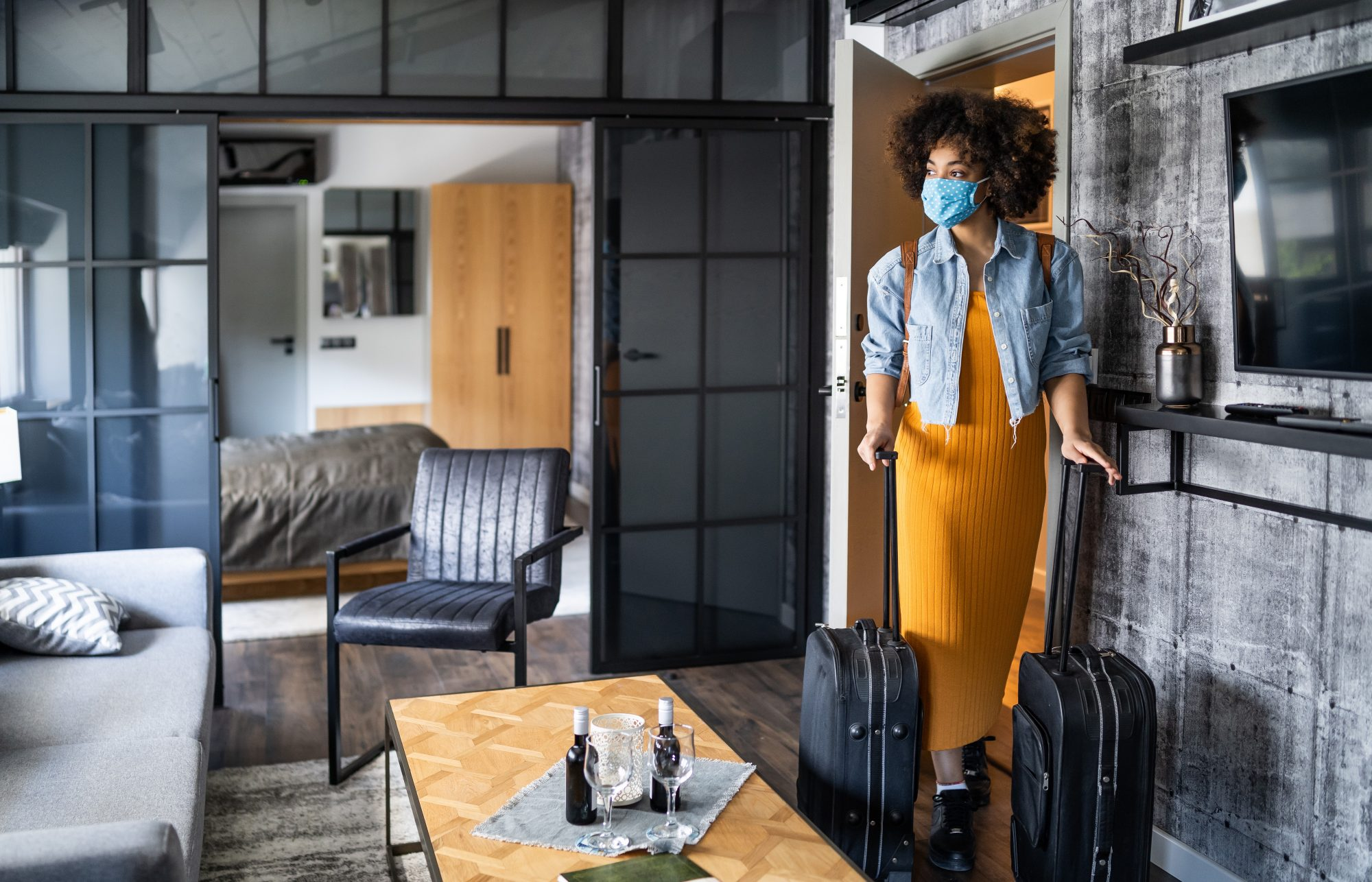 woman wearing a protective face mask arriving in hotel room