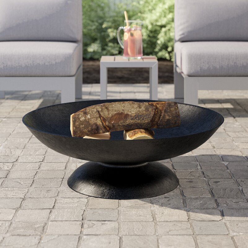 cast iron fire pit with logs on stone porch