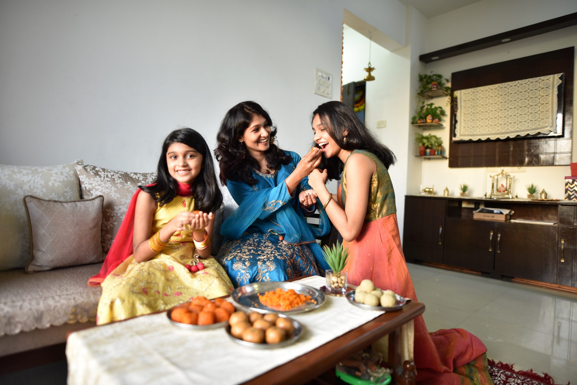 Mother and daughters tasting Indian sweet laddoos