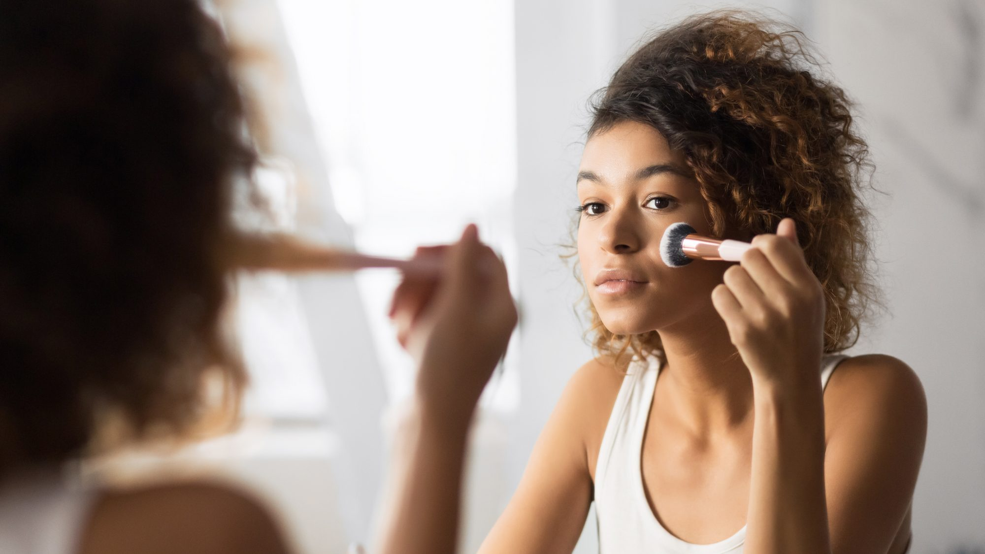 woman applying foundation with makeup brush in mirror