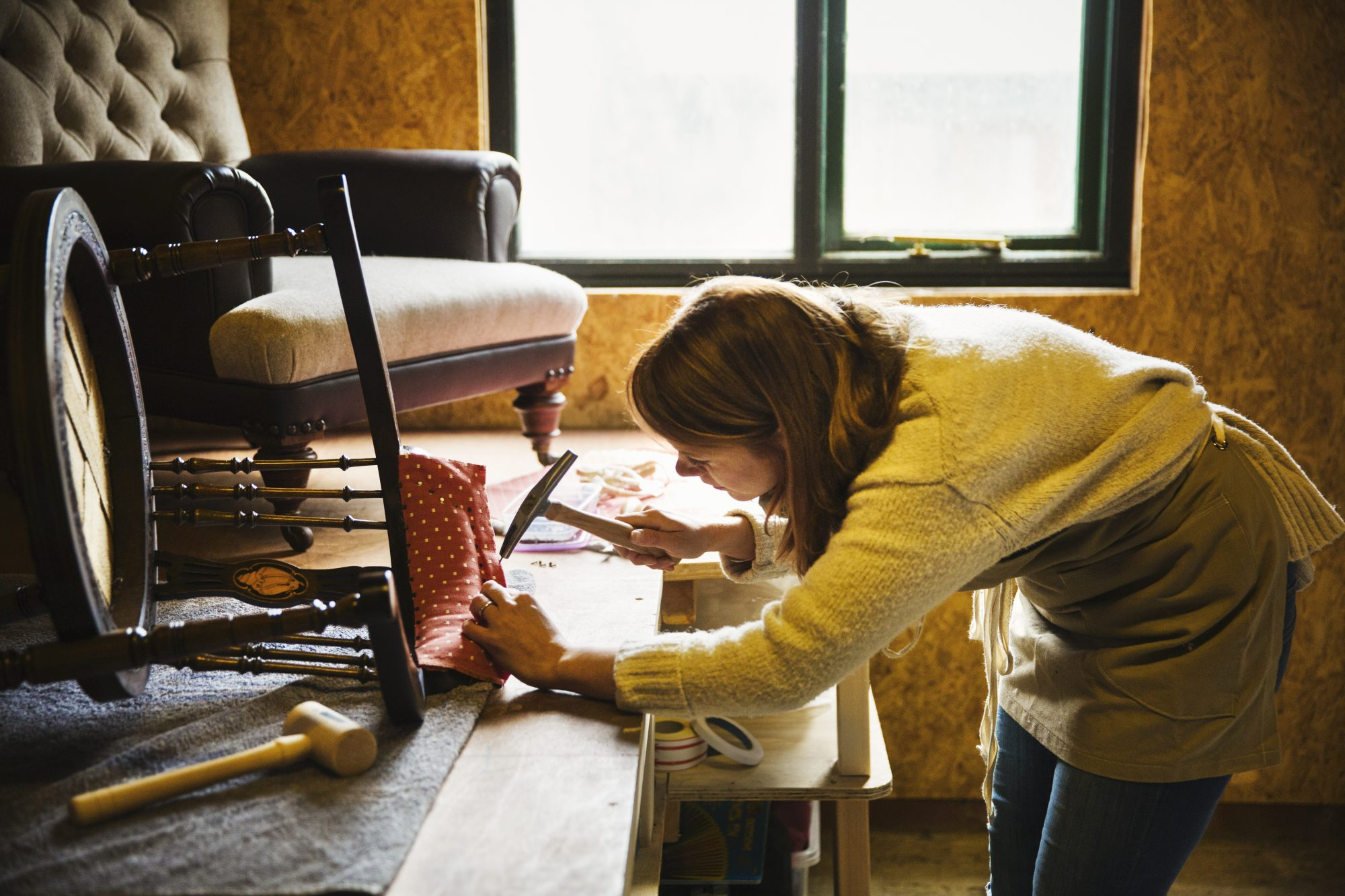 woman hammering fabric and padding to a chair frame in her upholstery workshop